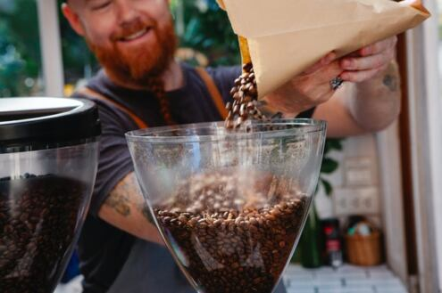 Amora Coffee review, a man pouring coffee from a bag into a grinder