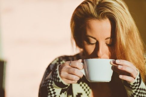 How long can coffee sit out, woman enjoying a cup of coffee
