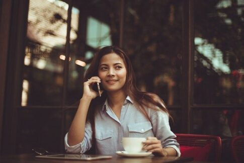 How much do coffee shop owners make, woman with a phone drinking coffee