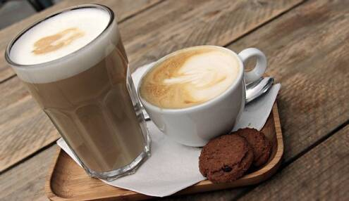 What is a cappuccino, caffe latte next to a cup of cappuccino