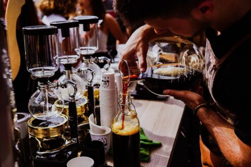 Cold brew vs iced coffee, a barista pouring cold brew coffee into a jar