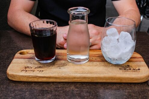 Cold brew vs iced coffee, a cup of cold brew coffee, a glass of cold water and some ice cubes