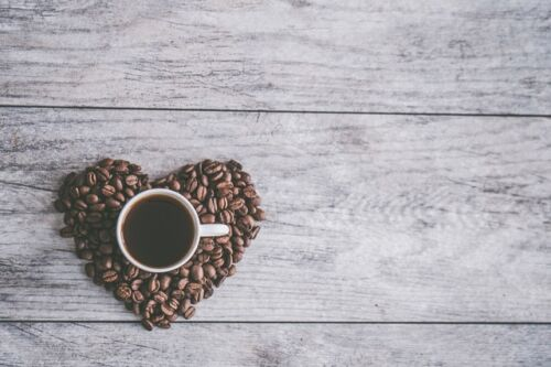 How Much Caffeine Is In a Can of Mountain Dew Compared to a Cup of Coffee, a cup of coffee and heart-shaped coffee beans