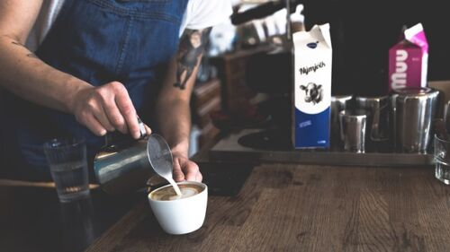 How long does coffee with milk or cream last in the fridge, barista pouring milk into a cup of coffee